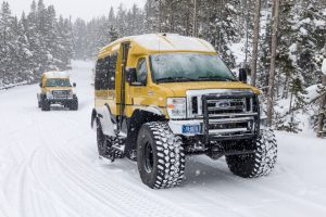A modern-day snowcoach-a van with oversized tires that are underinflated to keep the vehicle from sinking into the snow.